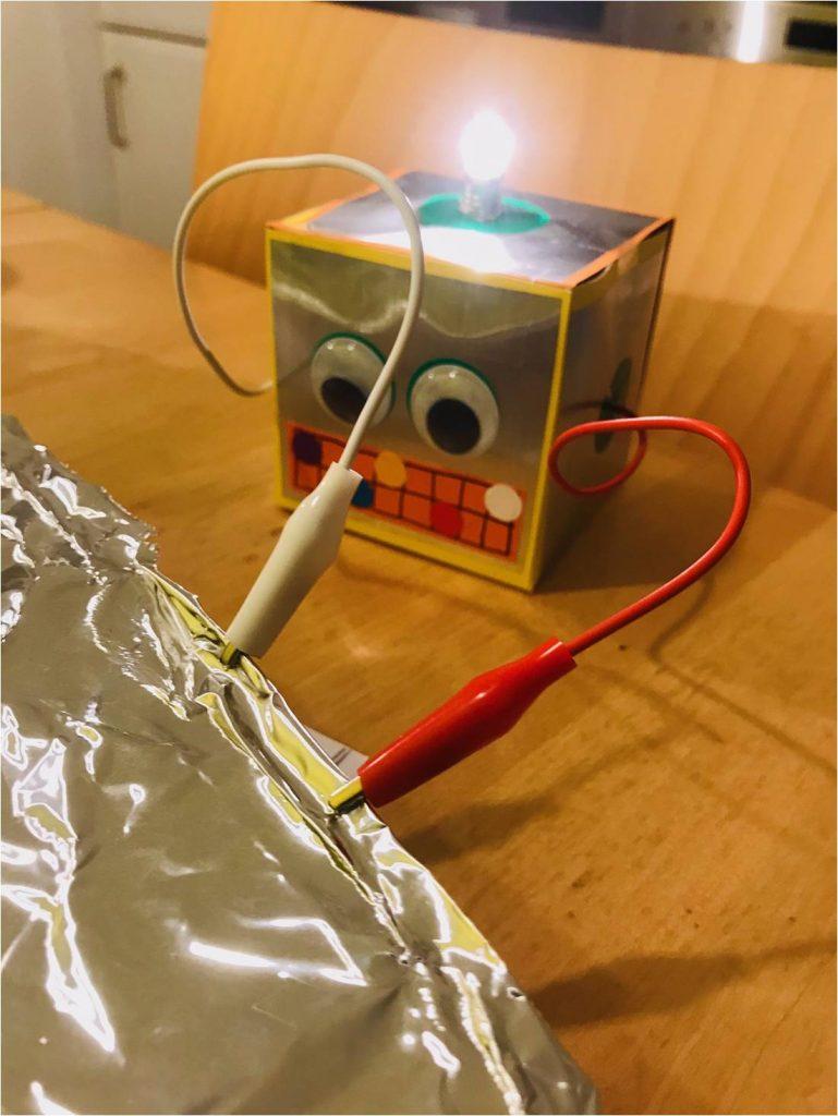 Ein Würfelroboter mit zwei Klemmen und einer leuchtenden Glühbirne auf dem Kopf.